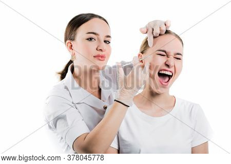 Beautician Makes Injection Of Filler To A Beautiful Young Girl On A White Isolated Background, Emoti