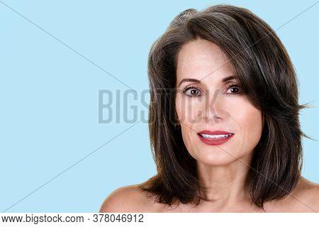 Portrait Of A Beautiful Mature Woman Against Light Blue Background