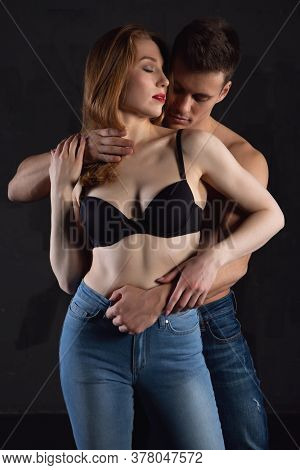 A Beautiful Young Couple In Love Tenderly Embraces On A Black Isolated Background. Male And Female T