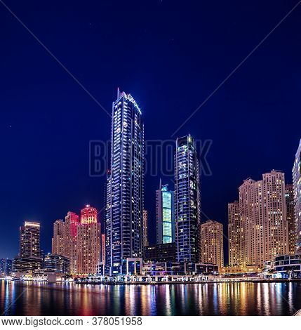 Dubai Marina At Night With Skyscrapers, Boats And Reflections In The Water, United Arab Emirates