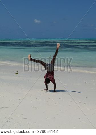 Young Black Boy Doing Handstand On Beautiful White Sand Beach With Turquoise Sea And Clear Blue Sky
