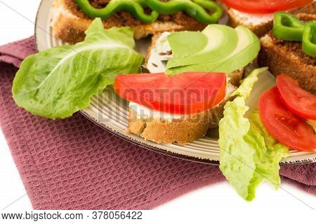 Sandwiches With Cheese, Sundried Tomatoes, Pepper, Avocado And Seeds, Lettuce, Lemon On Beige  Plate