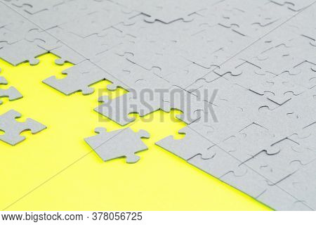 Unfinished Jigsaw Puzzle Pieces On Yellow Background.