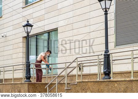 St. Petersburg, Russia. - July 21, 2020. The Janitor In The Medical Mask Washes Railing. Sanitary Tr