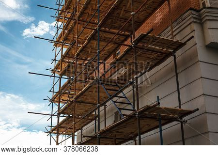 Building Under Construction With Scaffolds, House Renovation In Progress. Scaffolding On The Constru