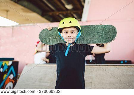 Boy Holding Skateboard Behind His Head. Cute Kid Smiling Outdoors With Skate Board. Childhood, Leasu