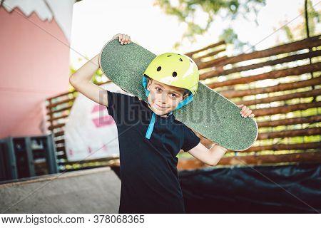 Portrait Boy Holding Skateboard Over Shoulder. Beautiful Kid Model Posing On Skate Board Park. Portr