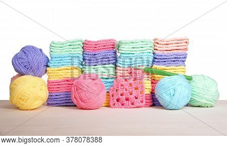 Piles Of Colorful Hand Crochet Granny Squares With Balls Of Yarn Piled Behind On A Light Wood Table,