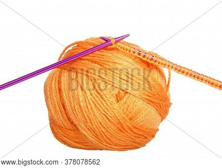 Purple Knitting Needles With Beginning Row Of Knitting Laying On Top Of Skein Of Bright Orange Yarn