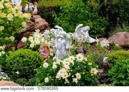 Garden Statues Of Angels And Birds On Flowerbed