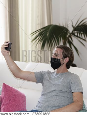 Handsome Young Man Using A Face Mask Sitting On A Sofa,holding His Phone Away And Looking At It On A