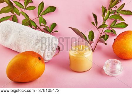 Scented Candle For Spa And Home With A Mango Scent And Green Leaves On A Pink Background.