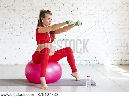 Pregnant Woman Working Out On A Fitness Ball With Dumbbells. Full-length Portrait