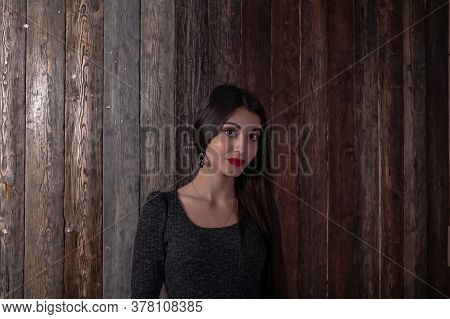 Beautiful Multicultural Young Woman Against Wooden Background. Portrait Of Pretty Young Muslim Woman