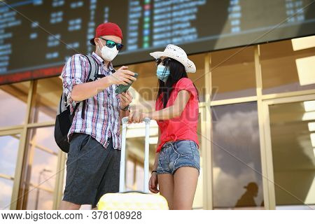 Woman In Hat Stand With Man On Train Station And Study Schedule In Phone And Scoreboard With Yellow