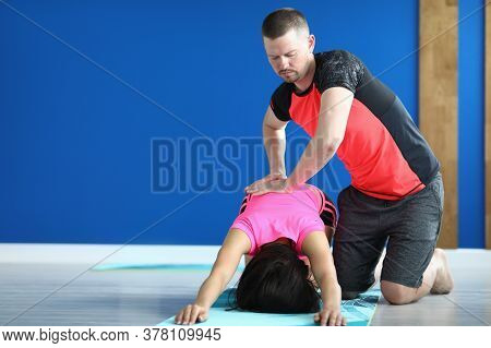 Trainer In Sports Uniform Press On Back Of Woman Who Istand In Pose On Mat. Man Stretch Back To Clas