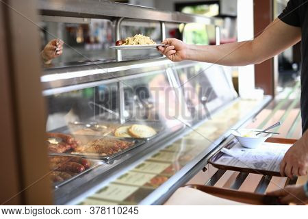 Man Stand Behind Counter Of Ready-made Food In Dining Room And Hold Plate With Lunch In His Hand. Pa