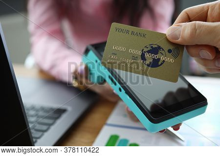 Man Make Cashless Payment. Gold Card Is Attached To Terminal. Woman Hold Terminal In Her Hand And Gi