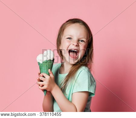 Frolic Happy Screaming 6-7 Y.o. Girl Kid In White T-shirt Holds With Both Hands Eats Big Vanilla Ice