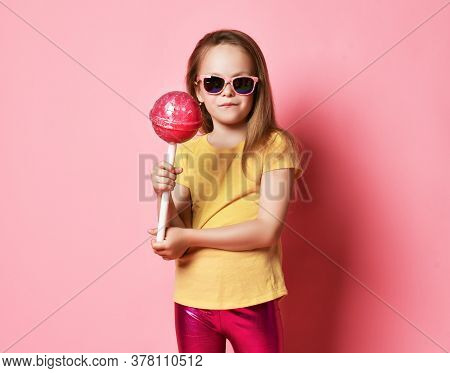 Frolic 6-7 Y.o. Kid Girl In Yellow T-shirt, Shiny Pink Leggings And Sunglasses Holds Big Heavy Pink