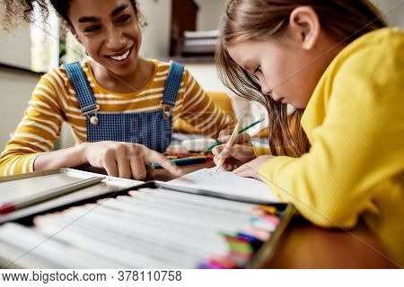 Close Up Of Caucasian Little Girl Spending Time With Her Nanny. Kid Is Writing, Learning How To Writ