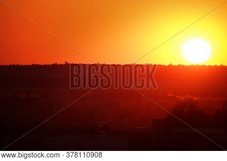 Big Hot Sun At Sunset, Descending Behind Horizon, Throwing Red And Orange Colored Light On Earth.