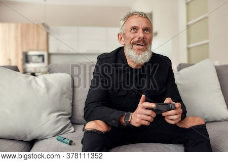 Bearded Middle-aged Man Holding Controller, Playing Video Games, Sitting On The Couch At Home. Weed