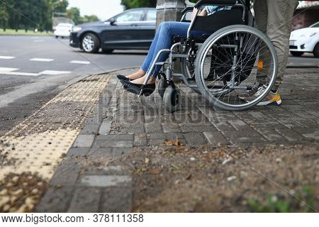 Female Legs In Wheelchair Close Up. Help For People With Physical Disabilities. Man Drive Wheelchair