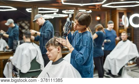 Barbershop Services. Side View Of Professional Barber Girl Serving Client, Drying Hair Of A Young Ma