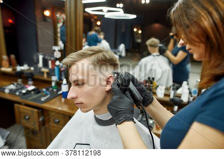 Professional Barber Girl Working With Hair Clipper, Serving Client. Young Guy Visiting Barbershop An