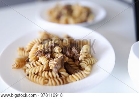Pasta And Meat Are On Plate. Two White Plate Of Food Stand On White Table. Cooking Delicacies At Hom