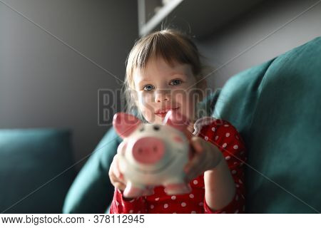 Girl In Red Dress With Polka Dots Sit On Couch And Smile. Child Hold Pink Piggy Bank In Her Hands An