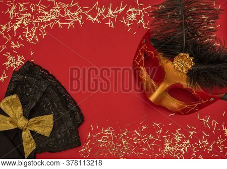 Christmas Red Background With Masquerade Mask, Confetti And Black Lace. Flat Lay Style. New Year Mas