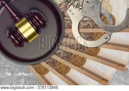 2000 Hungarian Forint Bills And Judge Hammer With Police Handcuffs On Court Desk. Concept Of Judicia