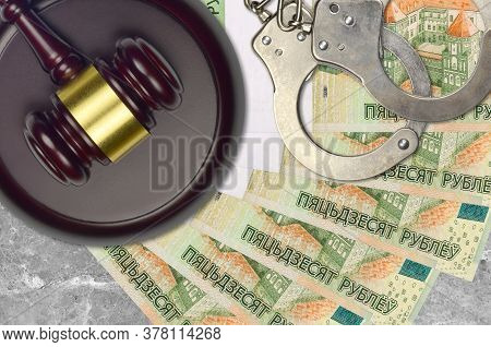 50 Belorussian Rubles Bills And Judge Hammer With Police Handcuffs On Court Desk. Concept Of Judicia