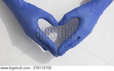 Doctors Hands Making Heart Shape Isolated On White Table With Shadows, Natural Lighting, Hands In Bl