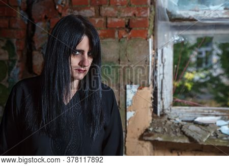 Portrait Of Young Beautiful Goth Woman In Black Dress Standing Near Broken Window In An Abandoned Ho