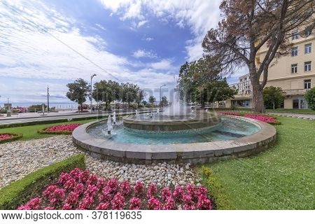 Opatija, Croatia - July 3, 2020 - Water Fountain In The Centre Of Opatija And Promenade By The Sea,