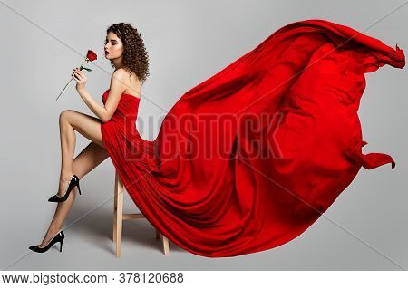 Beautiful Woman In Red Dress Smelling Roses Flowers, Fashion Model Studio Portrait On White, Flying