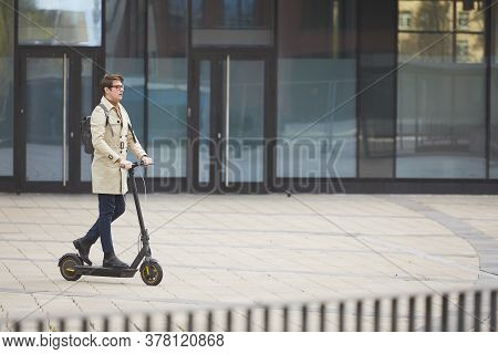 Wide Angle Portrait Of Modern Young Businessman Riding Electric Scooter While Commuting To Work With