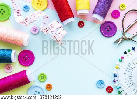 Sewing Accessories  On A Blue Pastel Background. Sewing Threads, Needles, Pins, Buttons  And Sewing