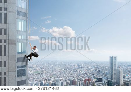 Businessman Climbs A Building With A Rope. Concept Of Determination.