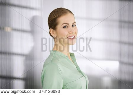 Beautiful Adult Business Woman Dressed In Green Blouse Standing Straight In Office. Business Headsho