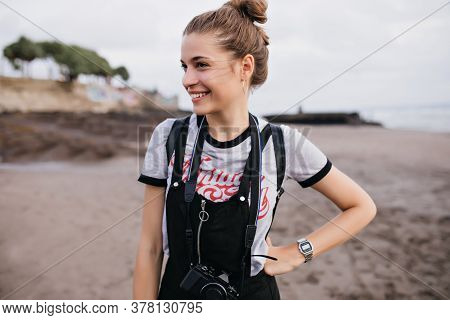 Graceful Female Photographer Standing In Confident Pose At Beach. Pleasant Girl In Trendy Wristwatch