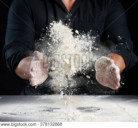 Chef In Black Uniform Sprinkles White Wheat Flour In Different Directions, Product Scatters Dust, Bl
