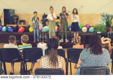 Childrens Holiday In Elementary School. Children On Stage Perform In Front Of Parents. Image Of Blur