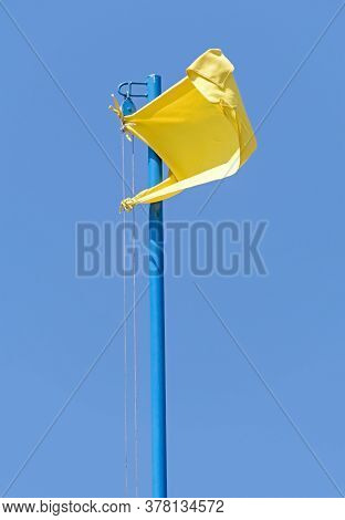 Yellow Flag Waving In The Breeze Against A Blue Sky