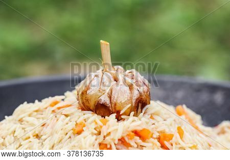 Cooking Rice Pilaf In A Large Cast-iron Pot On Fire. Garlic Bulb