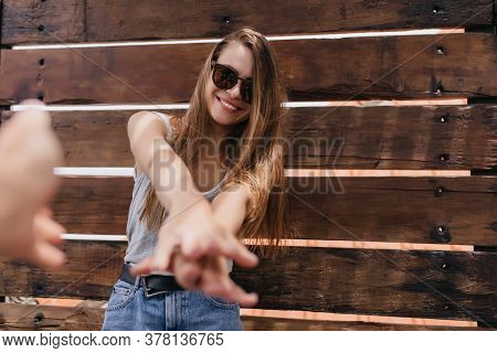 Blissful Young Woman In Casual Outfit Posing On Wooden Background And Laughing. Outdoor Portrait Of
