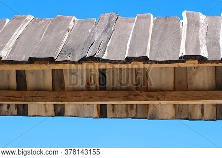 Part Of Narrow Wooden Roof Against A Blue Sky. Such Narrow Wooden Roofs Are Used For Decoration Abov